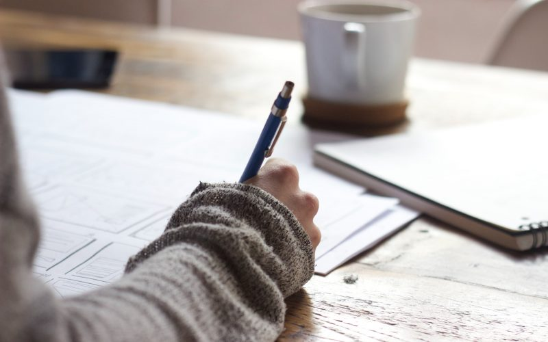 A picture of a woman writing with a pen